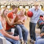 Gruppeaf unge mennesker har det sjovt med at bowle