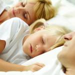 Lille pige sover mellem sine forældre - familie